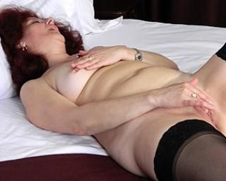Horny mature slut masturbating in a chair