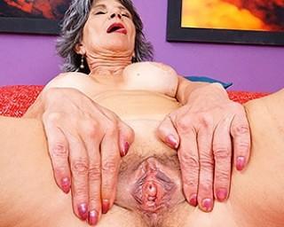 Horny mature slut masturbating on bed