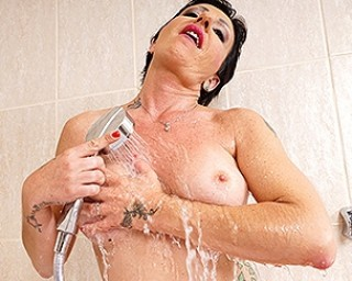 Horny housewife playing with her shaved pussy in the bathtub