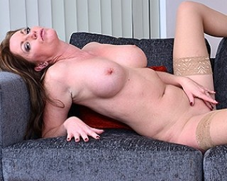 Horny MILF playing with her pussy on the couch
