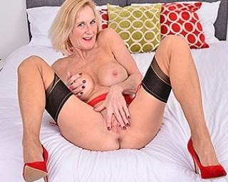 Naughty British cougar pleasing herself in bed
