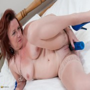 Horny mature lady playing on her bed with her toy